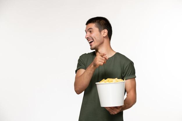 Widok z przodu młody mężczyzna w zielonej koszulce trzymając kosz z cipsami na białej ścianie film męski film samotny kino
