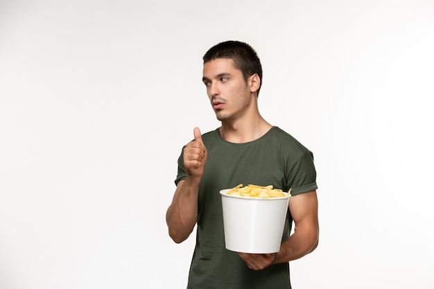 Widok z przodu młody mężczyzna w zielonej koszulce trzymając kosz z cipsami na białej ścianie film osoba mężczyzna samotny kino filmowe