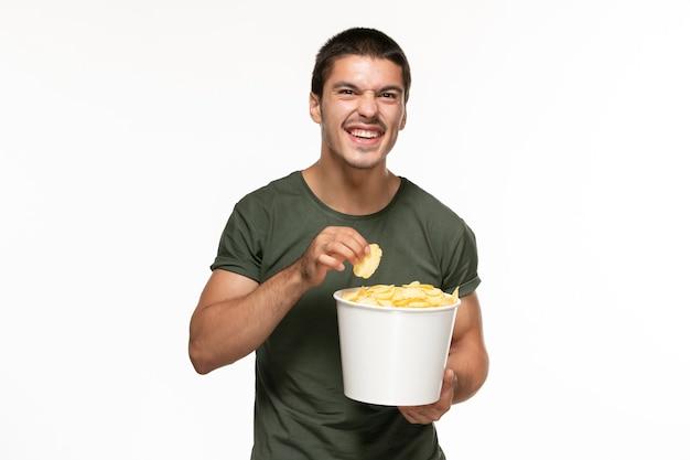 Widok z przodu młody mężczyzna w zielonej koszulce trzymając kosz z ziemniaczkami oglądając film na białej ścianie samotne kino filmowe
