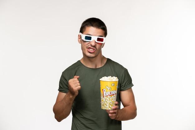 Widok z przodu młody mężczyzna w zielonej koszulce trzymając pakiet popcornu w d okulary przeciwsłoneczne na białej ścianie film samotny męski film kinowy