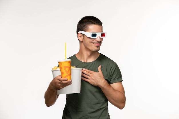 Widok z przodu młody mężczyzna w zielonej koszulce trzymający batoniki sodowe w okularach przeciwsłonecznych na białej podłodze film męski samotny film kino