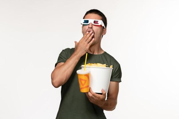 Widok z przodu młody mężczyzna w zielonej koszulce trzymający chipsy ziemniaczane i napoje gazowane w d okulary przeciwsłoneczne ziewający na białej ścianie film męski samotny film
