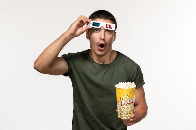 Widok z przodu młody mężczyzna w zielonej koszulce trzymający popcorn i zdejmujący okulary przeciwsłoneczne na białej ścianie film samotne kino męskie filmy