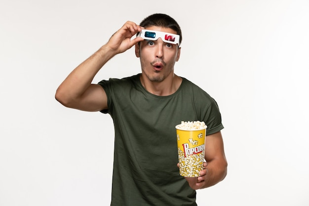 Widok z przodu młody mężczyzna w zielonej koszulce trzymający popcorn i zdejmujący okulary przeciwsłoneczne na białej ścianie film samotny kino męski film