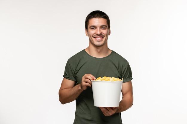Widok z przodu młody mężczyzna w zielonej koszulce z ziemniaczanymi kipsami oglądając film i uśmiechając się na białej ścianie film osoba mężczyzna samotny kino filmowe