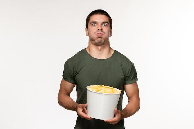 Widok z przodu młody mężczyzna w zielonej koszulce z ziemniaczanymi żetonami na białym biurku film osoba mężczyzna samotny kino filmowe