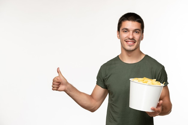 Widok z przodu młody mężczyzna w zielonej koszulce z ziemniaczanymi żetonami uśmiechnięty na białej ścianie osoba filmowa osoba samotna kino