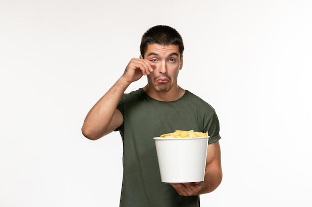 Widok z przodu młody mężczyzna w zielonej koszulce z ziemniakami i płacząc na białej ścianie film osoba mężczyzna samotny kino filmowe