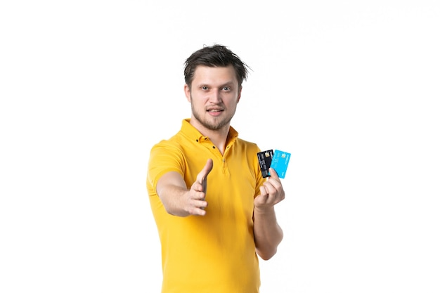 Widok z przodu młody mężczyzna w żółtej koszuli trzymający parę kart bankowych i próbujący uścisnąć dłoń na białym tle jednolity praca wydawanie pieniędzy kolor ludzki pracownik
