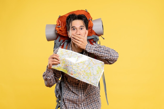 Widok z przodu młody mężczyzna wędrówki z plecakiem zszokowany na żółto