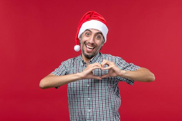 Widok z przodu młody mężczyzna wysyłanie miłości na czerwonym tle