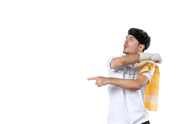 Widok z przodu młody mężczyzna z bandażem na zranionej ręce na białym tle sprawny sportowiec siłownia dieta sport kontuzja ciało styl życia szpital