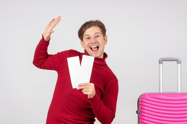Widok z przodu młody mężczyzna z biletami lotniczymi na białym tle