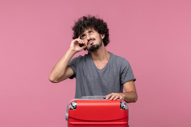 Widok z przodu młody mężczyzna z czerwoną torbą przygotowuje się do podróży po różowej przestrzeni