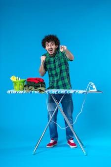 Widok z przodu młody mężczyzna z deską do prasowania na niebieskim tle dom ubrania czyste pralka żelazko prace domowe