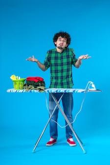 Widok z przodu młody mężczyzna z deską do prasowania na niebieskim tle prace domowe dom żelazne ubrania czysta pralka ludzka