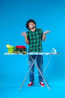 Widok z przodu młody mężczyzna z deską do prasowania na niebieskim tle prace domowe dom żelazne ubrania pralka ludzka