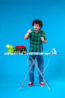 Widok z przodu młody mężczyzna z deską do prasowania na niebieskim tle prace domowe ubrania czysty ludzki dom pralka