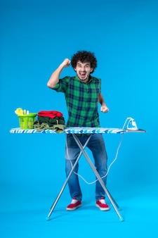 Widok z przodu młody mężczyzna z deską do prasowania radujący się na niebieskim tle prace domowe żelazne ubrania czysty dom pralka ludzka