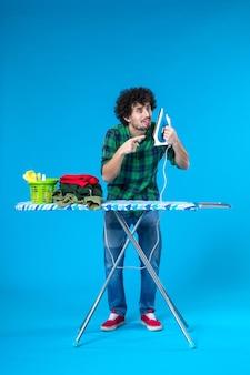 Widok z przodu młody mężczyzna z deską do prasowania trzymający żelazko na niebieskim tle kolory dom pralka czyste prace domowe człowiek