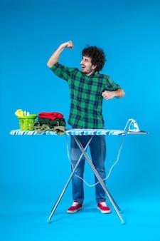 Widok z przodu młody mężczyzna z deską do prasowania wyginający się na niebieskim tle prace domowe dom żelazne ubrania czyste pralka ludzka