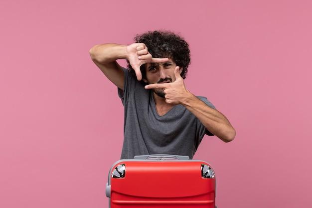 Widok z przodu młody mężczyzna z dużą czerwoną torbą przygotowuje się do podróży i pozuje na różowej przestrzeni
