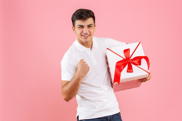 Widok z przodu młody mężczyzna z dużym prezentem świątecznym na różowym tle