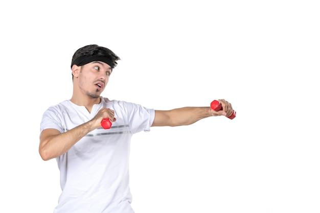 Widok z przodu młody mężczyzna z hantlami na rękach walczący z kimś na białym tle kolor ciało dopasowanie dieta zdrowie sportowiec joga człowiek styl życia sport
