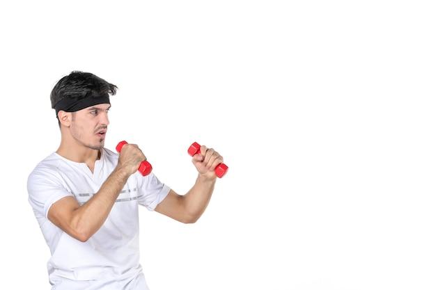 Widok z przodu młody mężczyzna z hantlami na rękach walczący z kimś na białym tle kolor ciało dopasowanie dieta zdrowie sportowiec joga styl życia sport