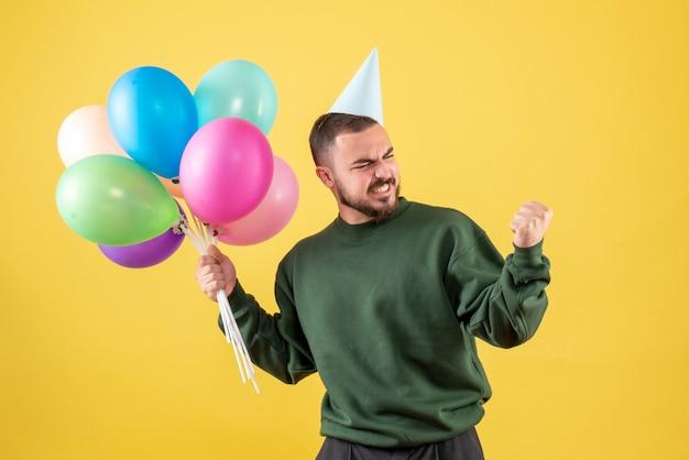 Widok z przodu młody mężczyzna z kolorowymi balonami na żółtym tle