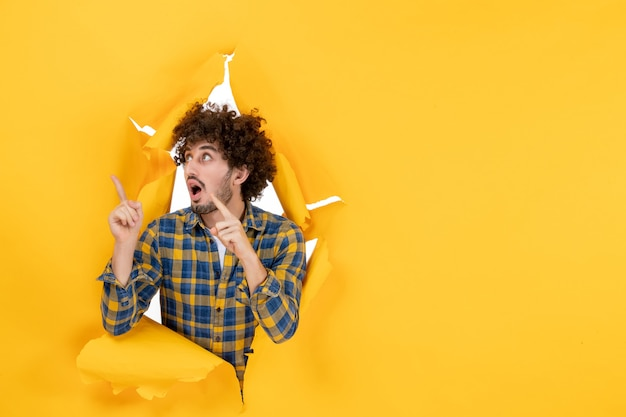 Widok z przodu młody mężczyzna z kręconymi włosami na żółtym podartym tle