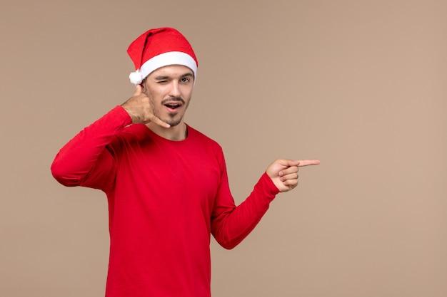 Widok z przodu młody mężczyzna z peleryną na brązowym tle emocji świąt bożego narodzenia