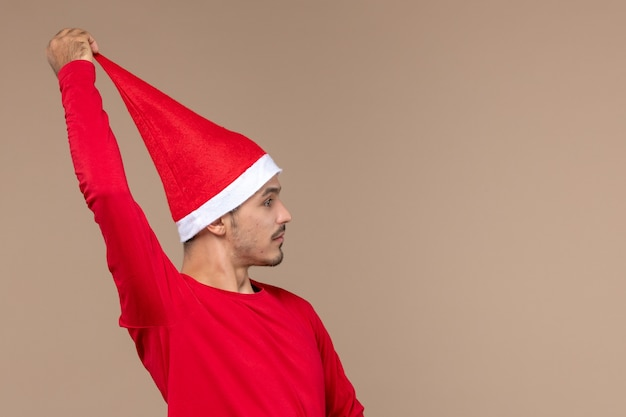 Widok z przodu młody mężczyzna z peleryną świąteczną na brązowym tle emocje świąteczne wakacje