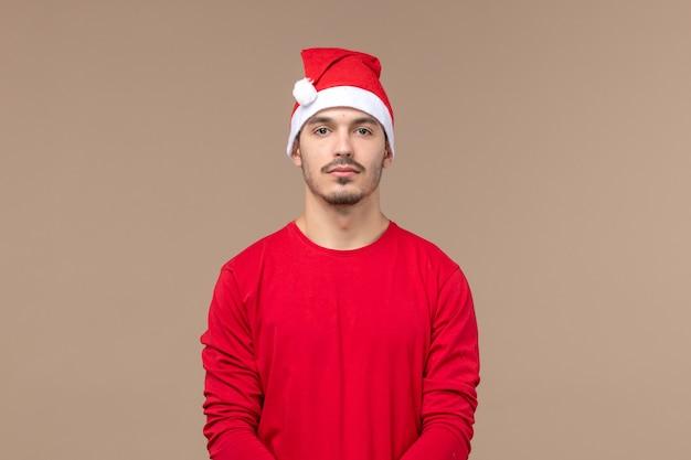 Widok z przodu młody mężczyzna z peleryną świąteczną na brązowym tle świąteczne emocje świąteczne
