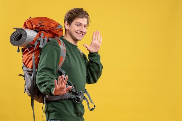 Widok z przodu młody mężczyzna z plecakiem przygotowującym się do wędrówek