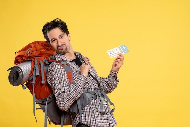 Widok z przodu młody mężczyzna z plecakiem trzymając bilet na żółto