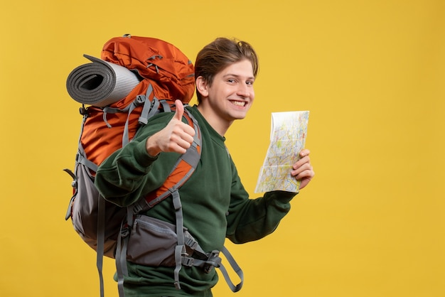 Widok z przodu młody mężczyzna z plecakiem trzymającym mapę