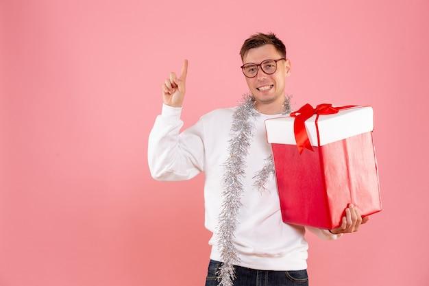 Widok z przodu młody mężczyzna z prezentem świątecznym na różowym tle