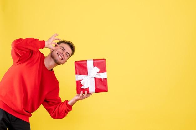 Widok z przodu młody mężczyzna z prezentem świątecznym