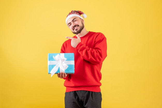 Widok z przodu młody mężczyzna z prezentem xmas na żółtym tle