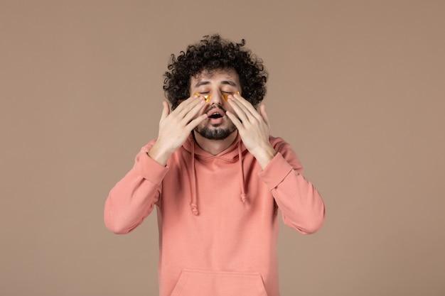 Widok z przodu młody mężczyzna z przepaskami na oczy na brązowym tle masaż skóry pielęgnacja skóry poziome spa
