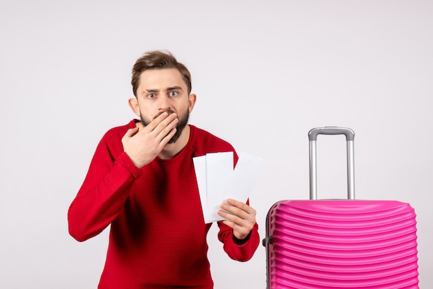 Widok z przodu młody mężczyzna z różową torbą i trzymając bilety na białej ścianie kolor podróży wakacje lot rejs letni turysta