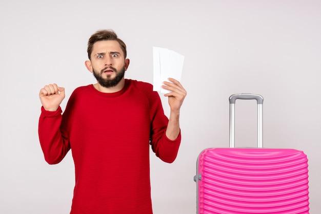 Widok z przodu młody mężczyzna z różową torbą i trzymając bilety na białej ścianie podróż podróż kolorową podróż turystyczną wakacje zdjęcie