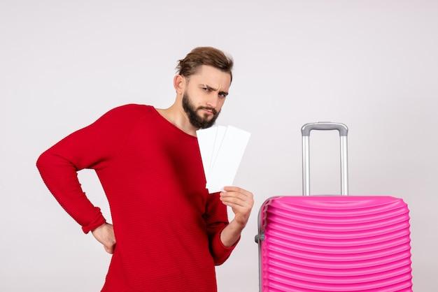 Widok z przodu młody mężczyzna z różową torbą i trzymający bilety na białej ścianie podróż lot kolor wycieczka podróż turystyczny wakacje zdjęcie