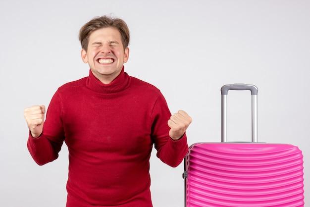 Widok z przodu młody mężczyzna z różową torbą na białym tle