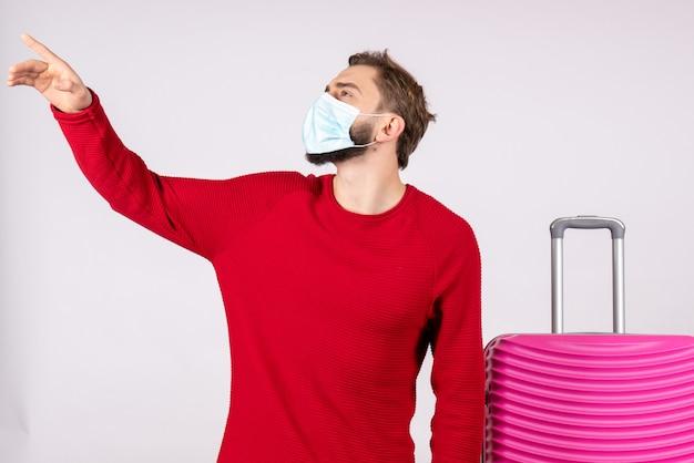 Widok z przodu młody mężczyzna z różową torbą w masce na białej ścianie podróż covid - wirus podróży wakacyjnych emocji lotu
