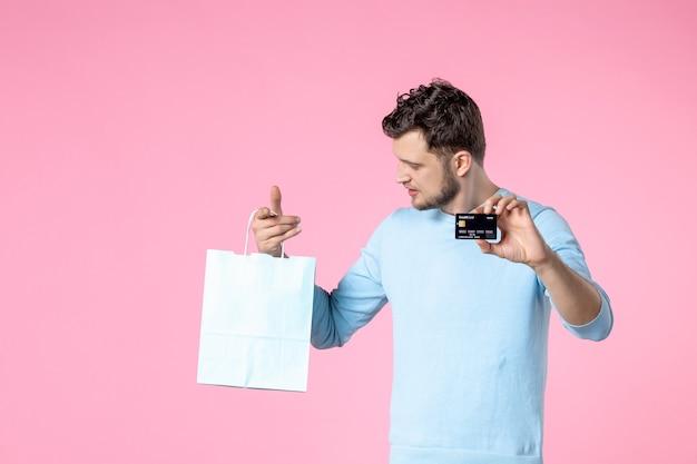 Widok z przodu młody mężczyzna z teraźniejszością i czarną kartą bankową na różowym tle równość data małżeństwa dzień kobiet marzec miłość kobieca zabawa zmysłowa