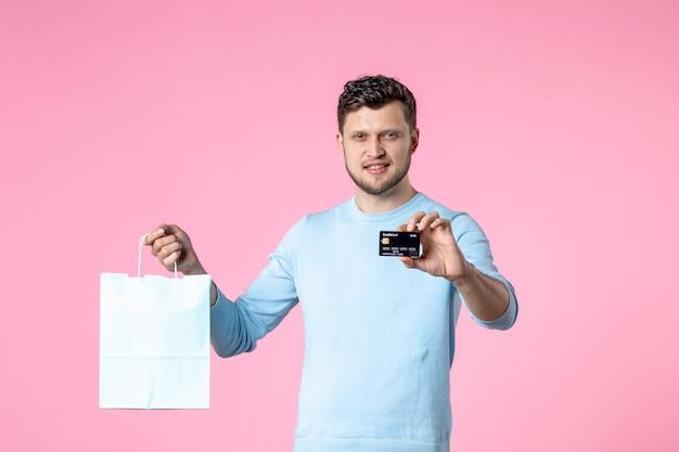 Widok z przodu młody mężczyzna z teraźniejszością i czarną kartą bankową na różowym tle równość data małżeństwa dzień kobiet marzec miłość kobieca zabawa zmysłowy park