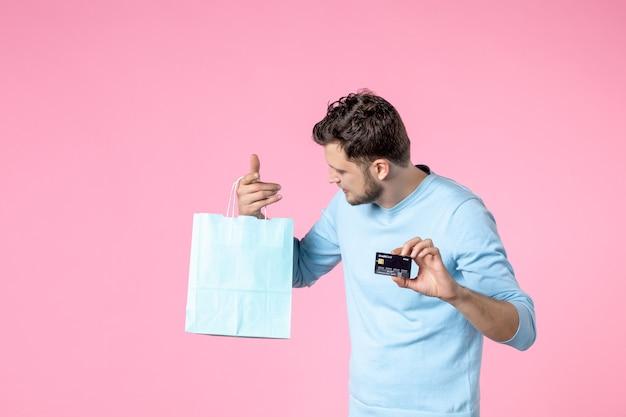 Widok z przodu młody mężczyzna z teraźniejszością i czarną kartą bankową na różowym tle równość małżeństwo dzień kobiet marsz miłość kobieca zabawa zmysłowa randka