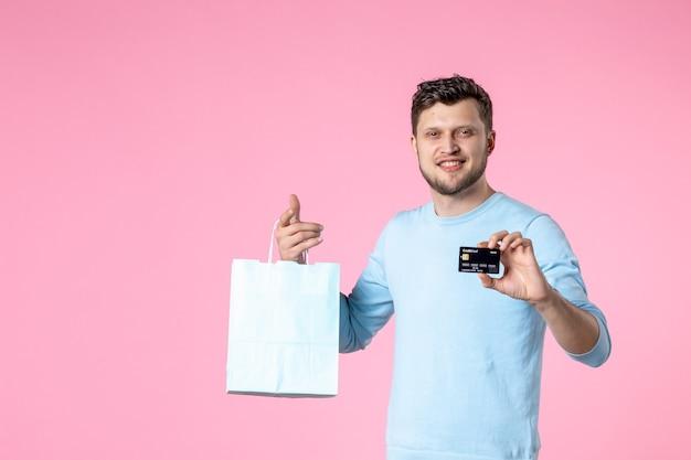 Widok z przodu młody mężczyzna z teraźniejszością i czarną kartą bankową na różowym tle równość małżeństwo dzień kobiet marzec miłość kobiecy park rozrywki data